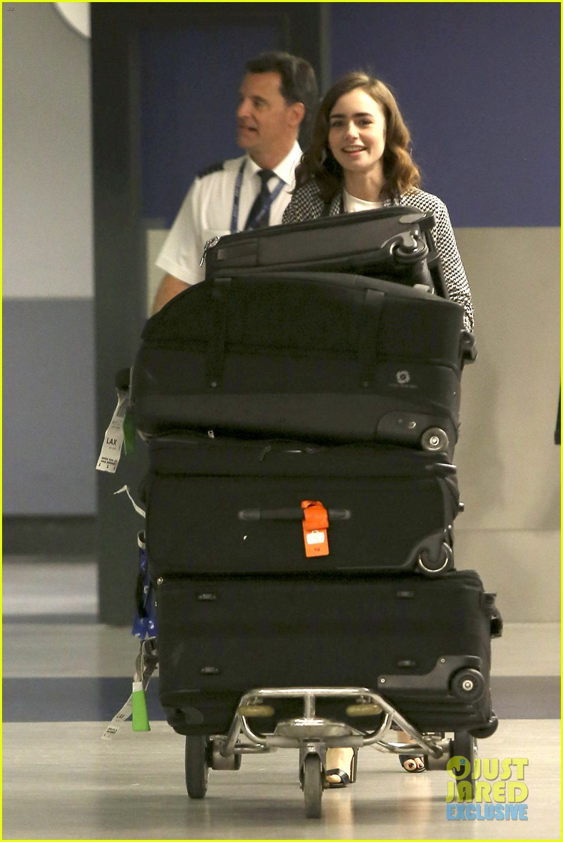 lily collins pushes giant luggage cart after mortals tour 032939604