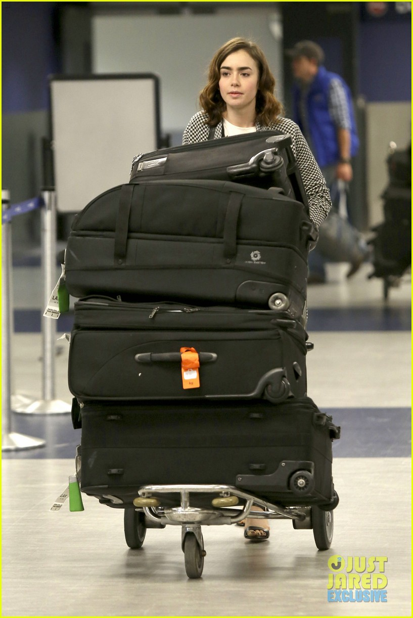 lily collins pushes giant luggage cart after mortals tour 06