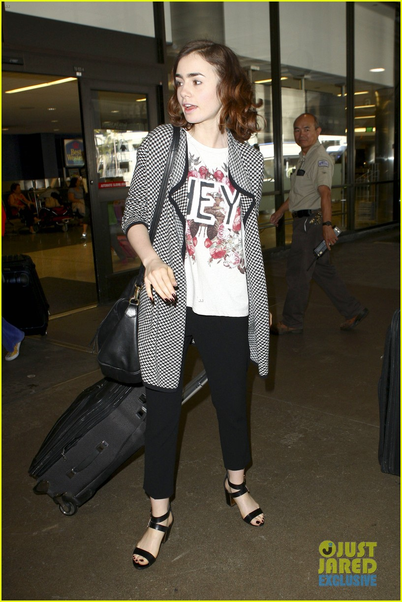lily collins pushes giant luggage cart after mortals tour 23