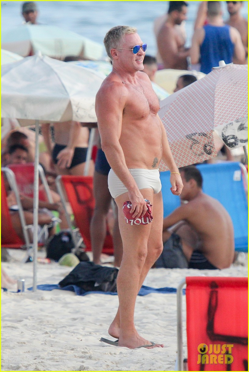 sam champion strips off board shorts to show speedo 01