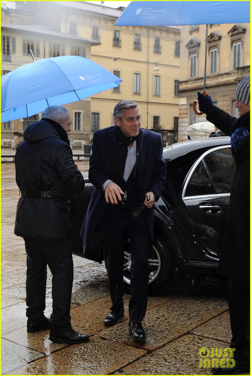 matt damon george clooney get personal umbrella holders in milan 11