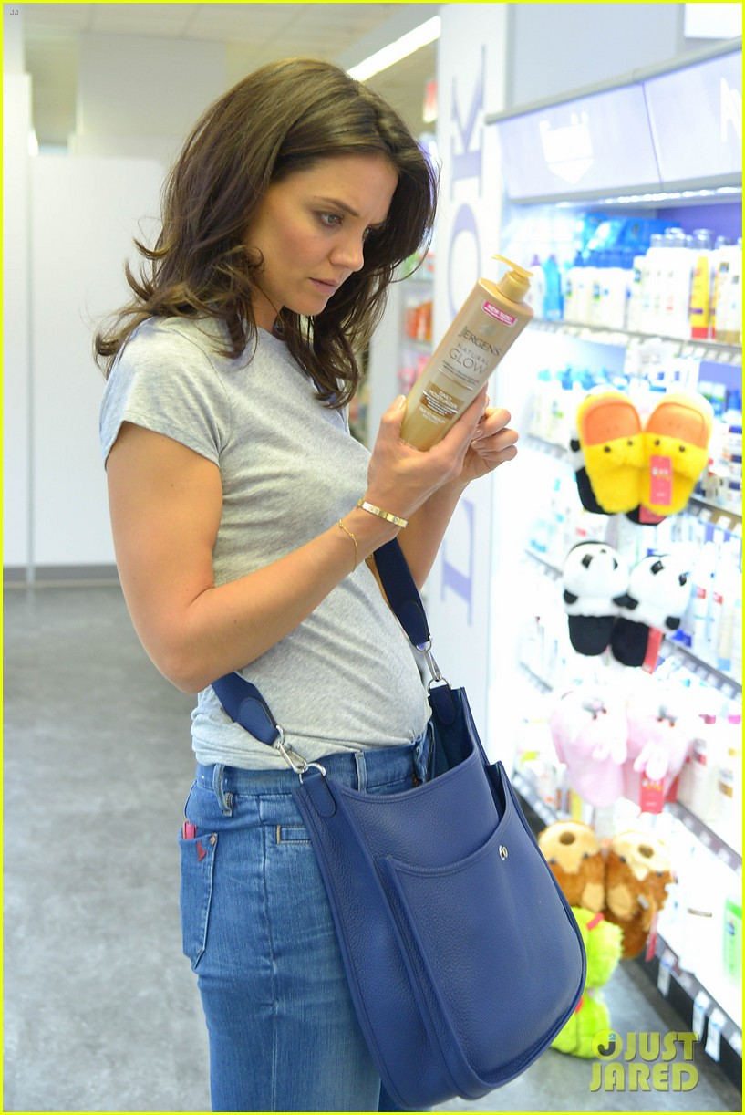 katie holmes intensly examines a bottle of tanning moisturizer 03