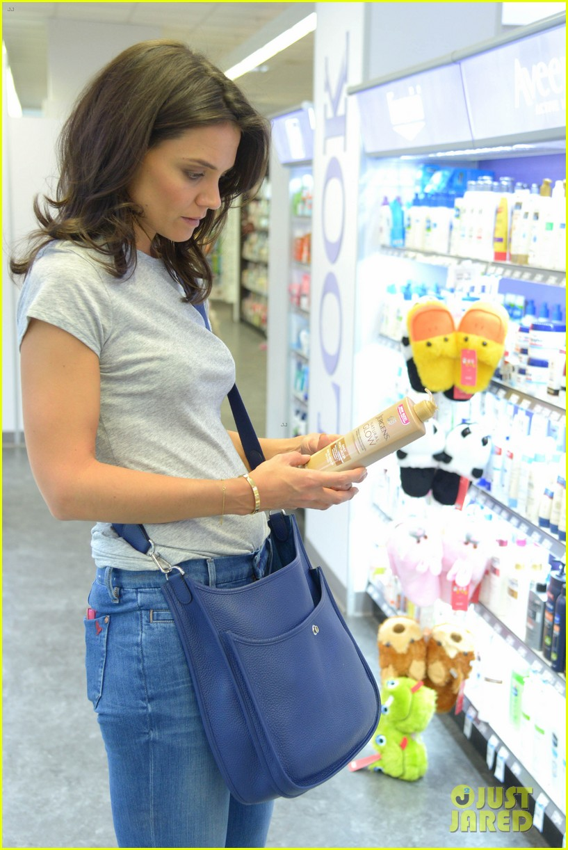 katie holmes intensly examines a bottle of tanning moisturizer 04