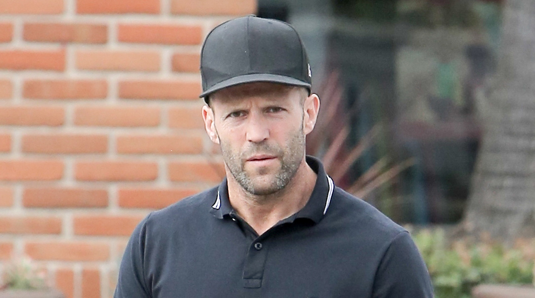 Jason statham rocks a cap to hide his new no eyebrows look during a