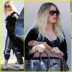 Khloe Kardashion Holds Clothes Over Baby Bump to Cover Up