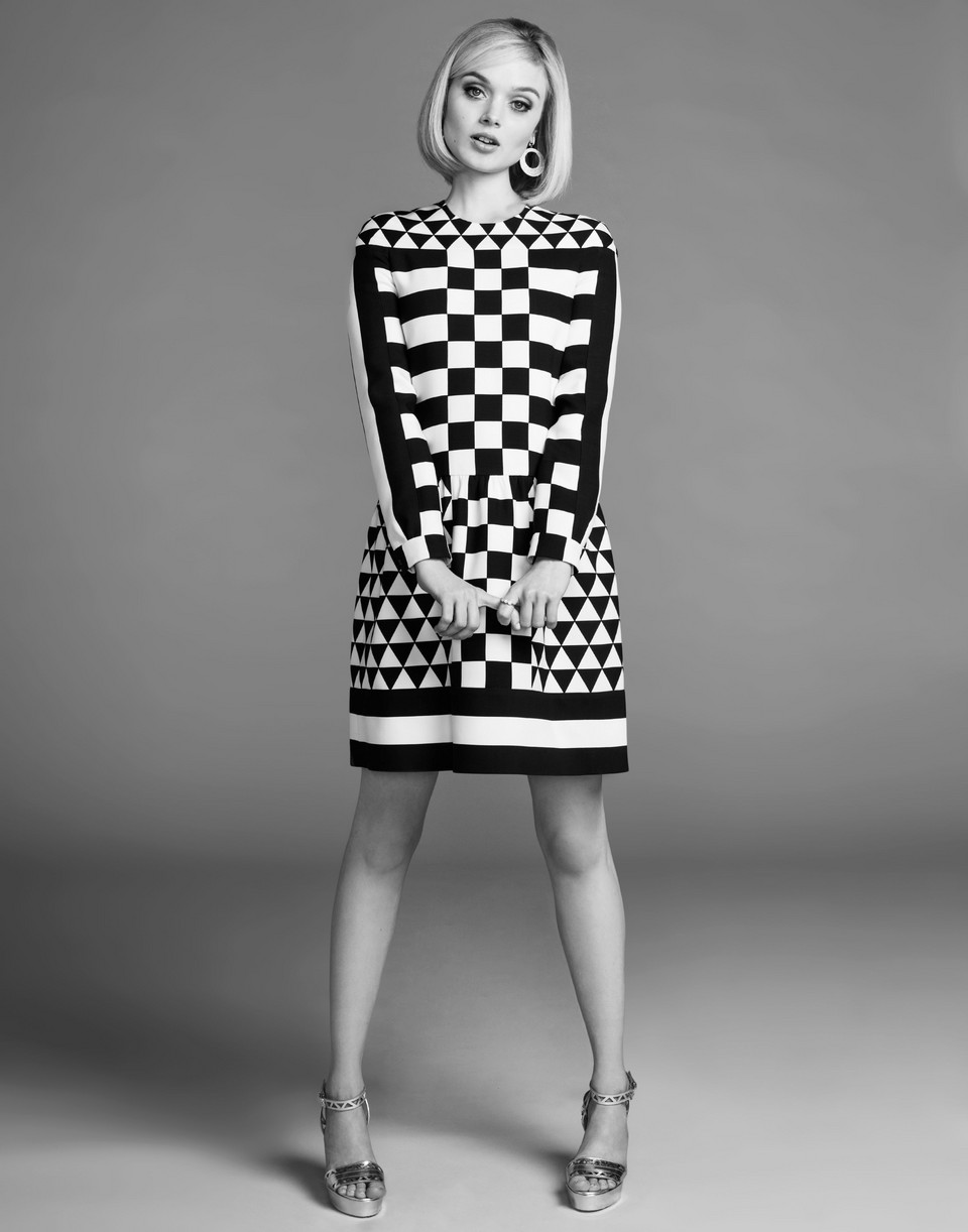 Bella Heathcote standing in a black and white patterned dress