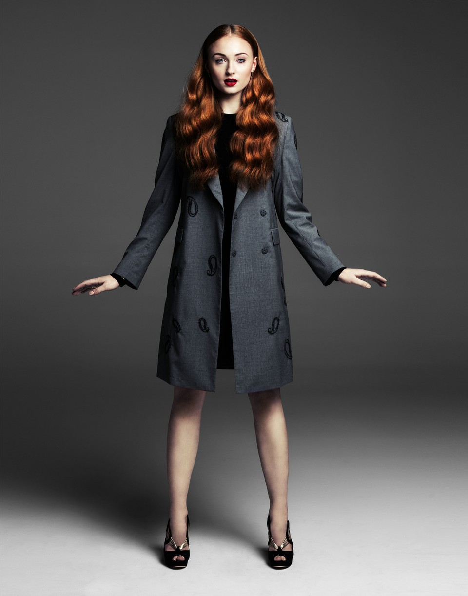 Sophie Turner wears a coat in a full length color portrait