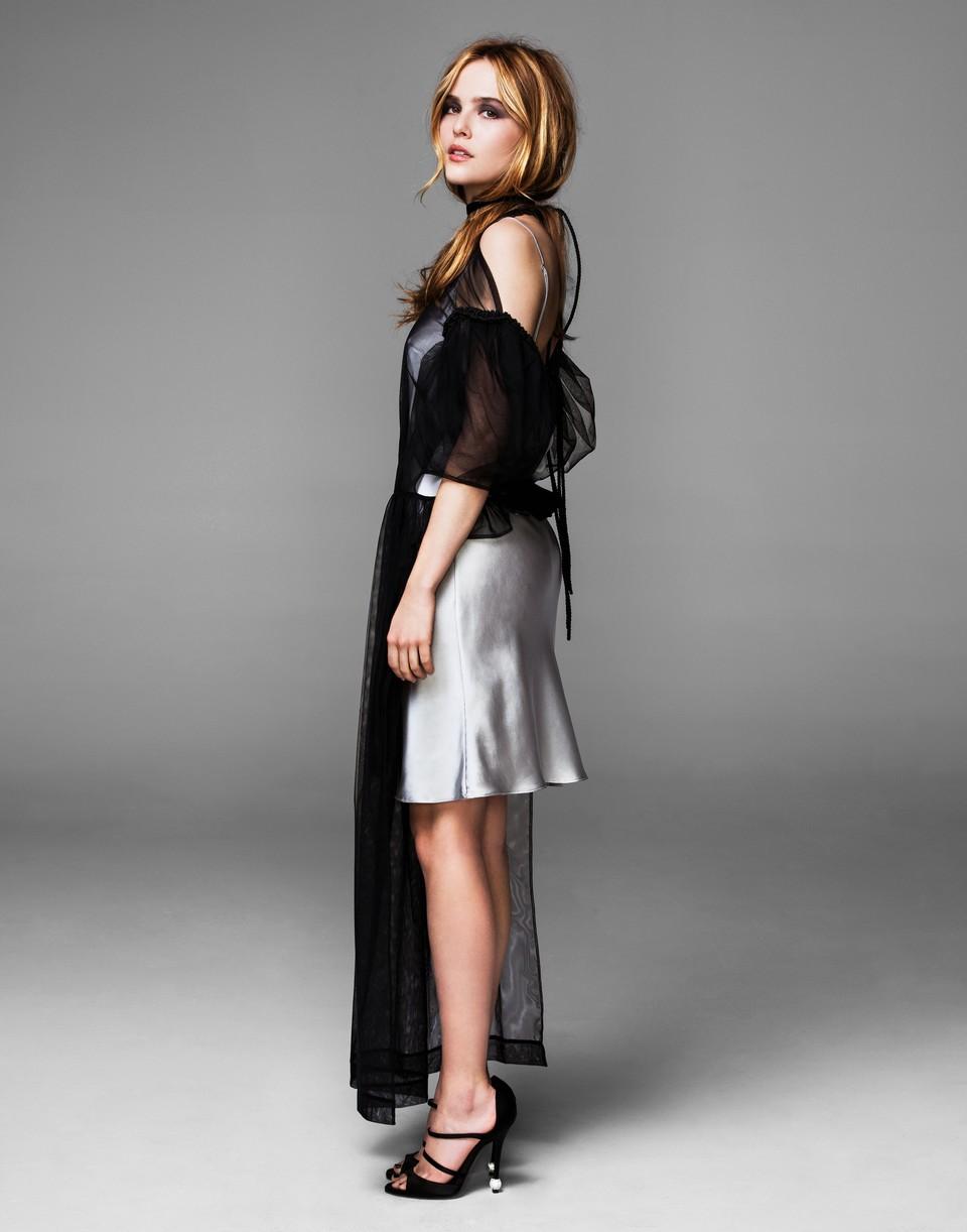 Zoey Deutch wears an apron dress over a silk dress